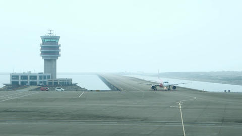 Aircraft taxiing at taxiway at water, pass control tower, time lapse shot Footage