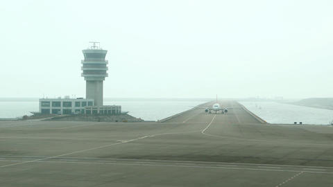 Aircraft taxiing towards camera, move along taxiway, beside control tower Footage