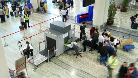 X-ray scanner in airport, manual inspection desk, staff work, passengers Live Action