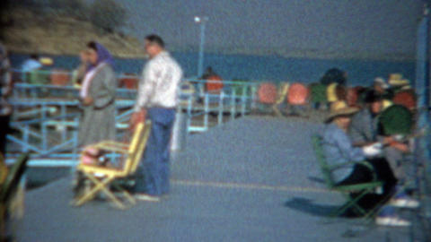 1964: Folks fishing off colorful pier in blue waters lake Footage