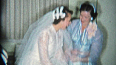 1964: Bride showing off garter belt in wedding dress her wedding party Footage