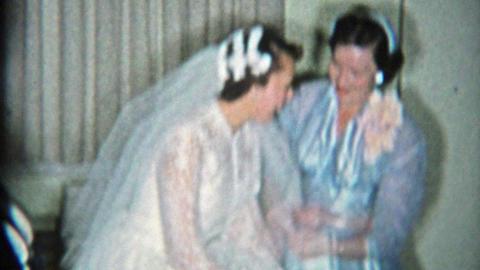 1964: Bride showing off garter belt in wedding dress her wedding party Footage