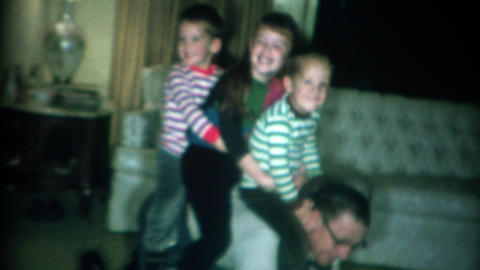 1966: 3 kids having fun riding dad like a horse in the living room Footage