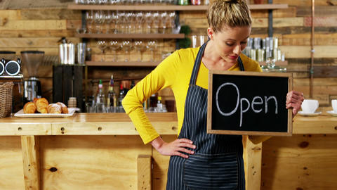 Waitress showing slate with open sign in cafe Live Action