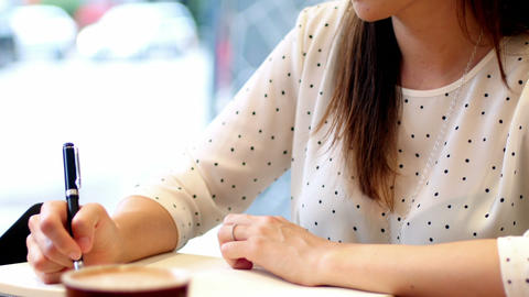 Businesswoman writing in diary Live Action