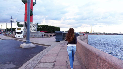 Cheery woman run along embankment to Spit of Vasilyevsky Island, POV follow Footage