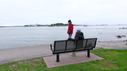 Woman rest alone at shore, sit on bench, man walk at waterfront path Footage