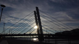 Black silhouette of modern cable-stayed bridge against evening sky and sun Live Action