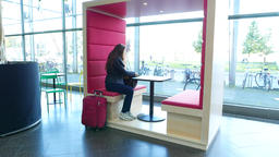 Woman come to rest at small semi-private bench with table, modern style Footage