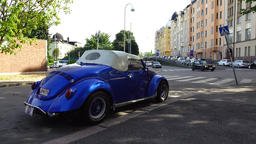 Cabriolet car with canvas top parked at old city street, rear side view Footage