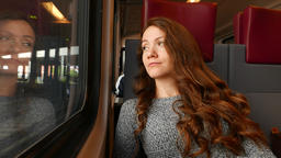 Calm woman travel in modern comfortable suburban train, look out of window Footage