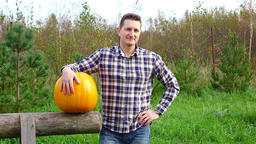 Young adult provincial proud of good harvest, stand with large pumpkin Footage