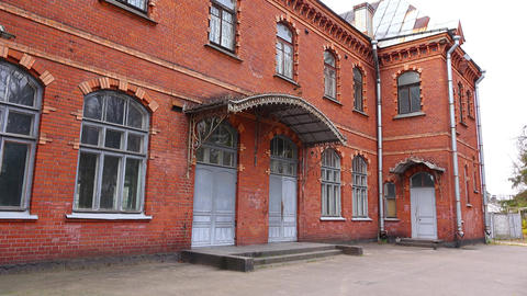 Old and empty red brick building of railway station, establishing shot Footage