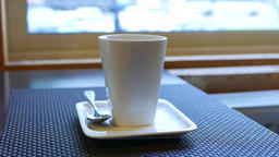 High white tea cup stand on small square dish, blurred window on background ライブ動画