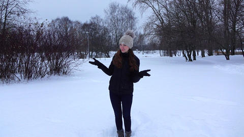 Merry girl catch snowflakes by hands, happy pose on camera, slow motion shot Footage