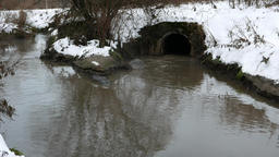 Dirty waters from drainage pipe outlet fall into muddy contaminated river Footage