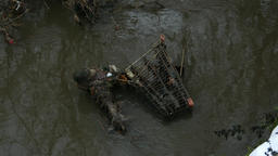 Trashed shopping cart half sink in dark dirty water stream of muddy river Footage