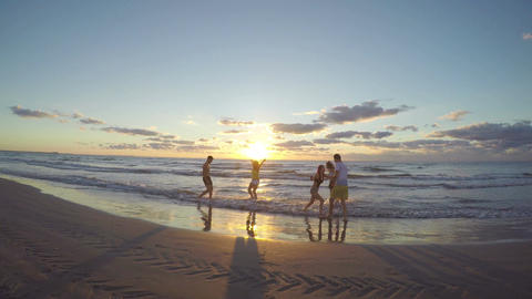 Group of friends running on a sandy wet beach towards the sea and teasing each o Live Action