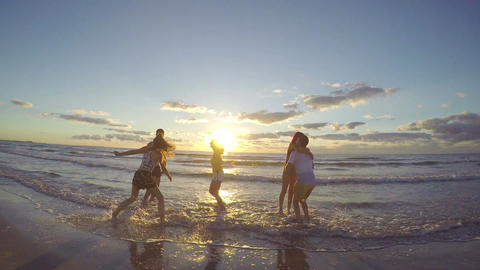 Group of friends running towards the sea on a beautiful beach at sunrise Footage