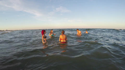 Group of friends playing volleyball in the water Footage