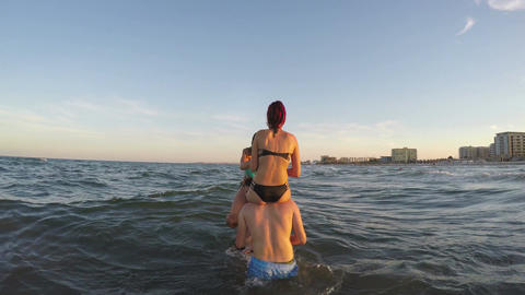 Couples playing in the sea - guys carrying their girls on their shoulders Footage