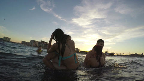 Couples having fun in the sea - guys carrying girls in their arms Footage