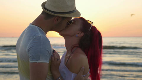 Young beautiful couple kissing at sunrise on the beach Footage