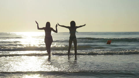 Silhouettes of two women dancing on the shore of a sandy beach Footage