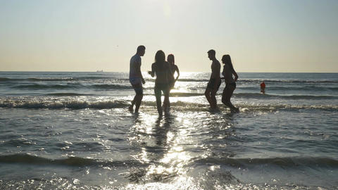 Group of friends running towards the sea and dancing with their feet in the wate Footage