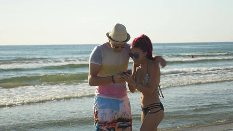 Couple taking selfie and having fun on the shore of a sandy beach Footage