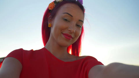 Young beautiful redhead posing on a beach and taking a selfie Footage