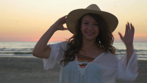 Young beautiful happy woman posing on the beach at sunset Footage