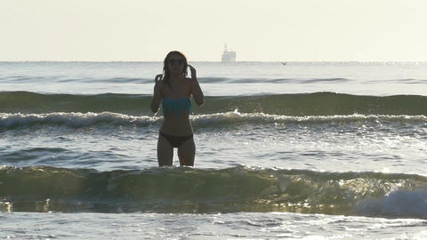 Young caucasian woman running in the water towards beach in slow motion Footage