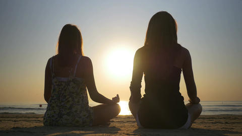 Two women meditating on the shore of the sea Footage