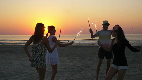 Group of friends dancing with fireworks on a sandy beach at sunrise Footage