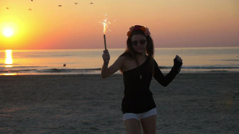 Young beautiful teenager female dancing in the twilight on a beach with a firewo Footage