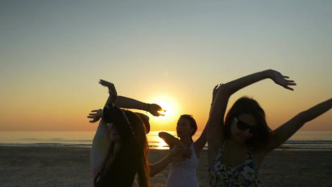 Friends dancing happily and waving their hands in the air at the beach at sunris Footage