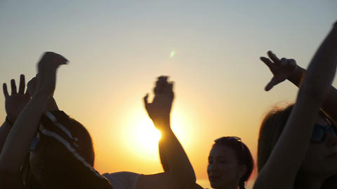 Young teenagers waving their hands in the air at sunset Footage