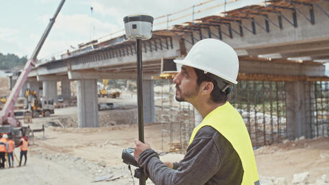 Construction engineer using a GPS device at a construction site Footage