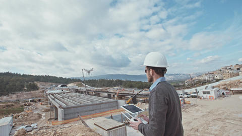 Man operating a drone for aerial photography in a constructions site Footage