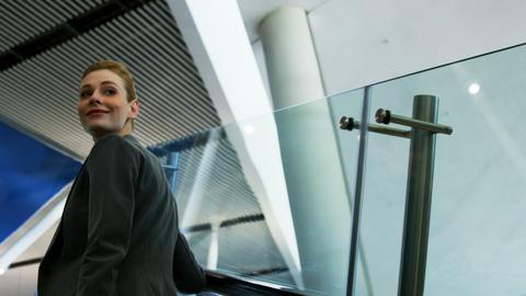 Businesswoman standing on an escalator Footage