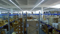 Camera moves past shelves boxes in storage warehouse interior HD video Footage