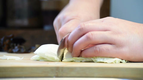Close-up of professional chef hands using knife to roughly chop Chinese cabbage Footage