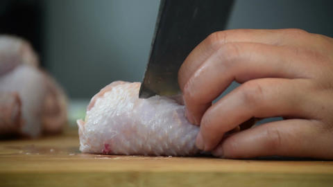 Slow-Motion chopping chicken drumstick for cooking Live Action