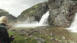 Woman admiring waterfall in Rondane National Park, Norway Footage