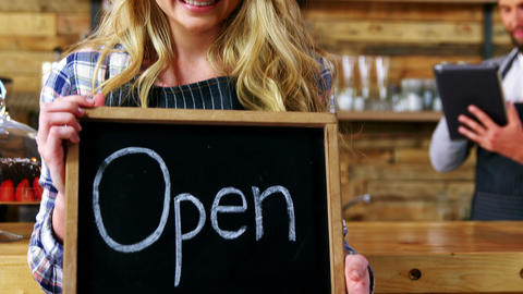 Smiling waitresses holding open sign board Live Action