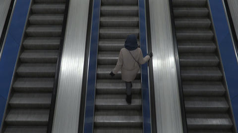 Girl moves up on escalator view from above Footage