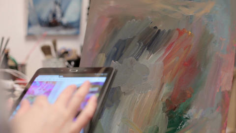 Artist in her studio using a digital tablet to surf the web Footage