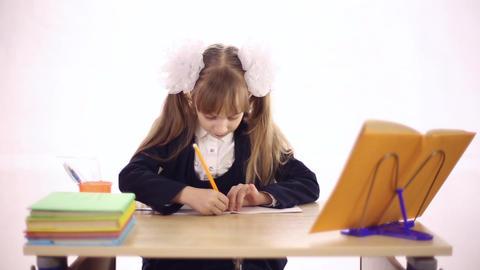 Schoolgirl sitting at school desk Image