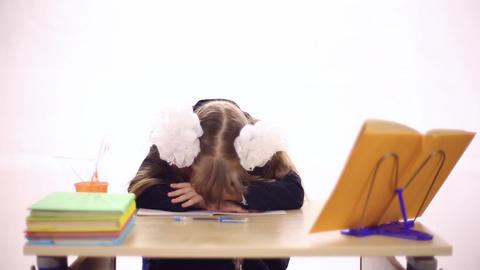 Schoolgirl sitting at school desk Live Action